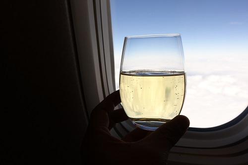 飛行機でシャンパンを飲む